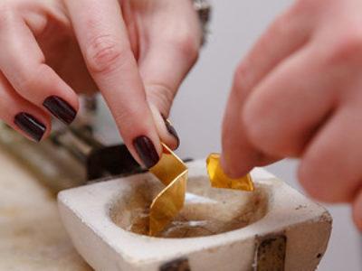 Noivos colocam juntos no cadinho o ouro das suas futuras alianças.